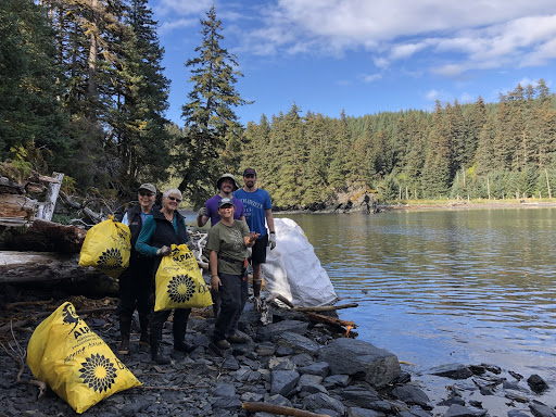 A group of people holding yellow bags on a shoreline lined with evergreen trees.