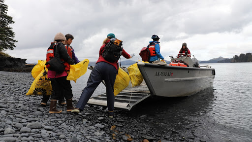 A group of people on a rocky shoreline hauling large, plastic yellow bags onto a boat.