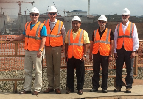 A group of five people standing in orange vests and hard hats in front of a construction site.