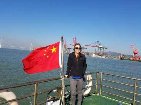 A woman next to a Chinese flag with water and an industrial shoreline in the background.
