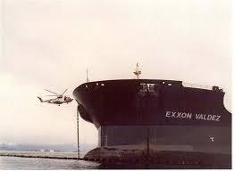 "A black and white photo of a helicopter approaching with a vessel with the name ""Exxon Valdez"" on it."