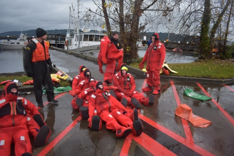 A group of people in red survival suits lined up together sitting on concrete with a dock in the background.