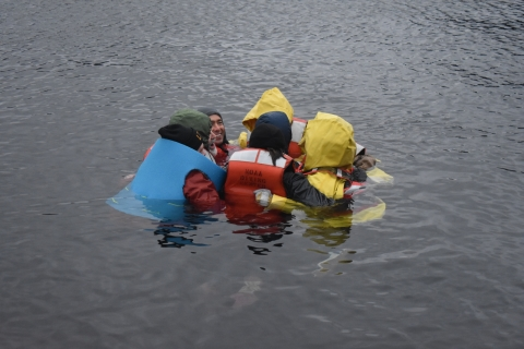 A group of people huddle together in water.