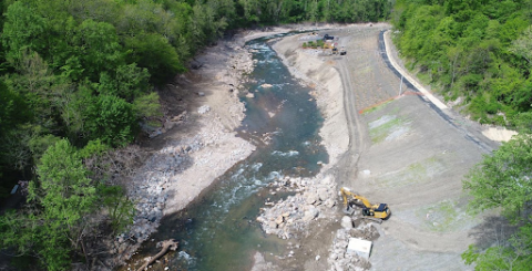 An aerial view of a construction vehicle working alongside a river.