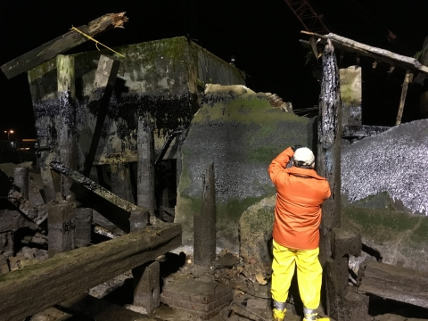 A man in response gear inspects an oiled pier.