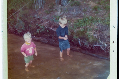 Two children standing in water.
