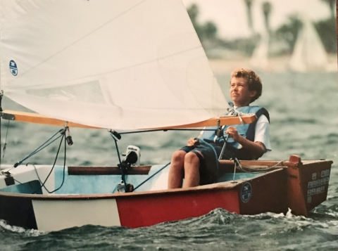 A young boy on a small sailboat.