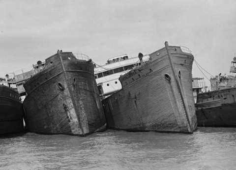 A black and white photo of two wooden ships tied together.