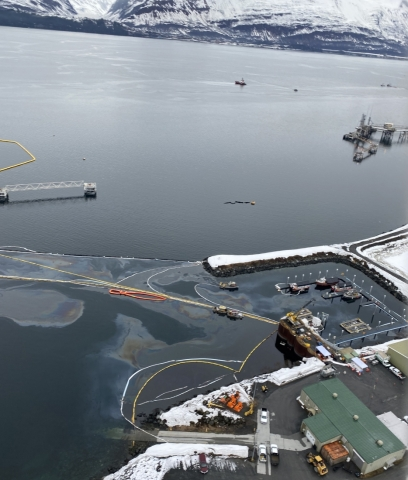 An aerial view of oil in a marina with pollution boom around it.