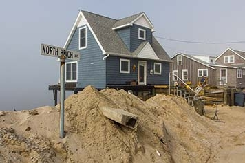A house raised above a sandy shoreline with debris in it.