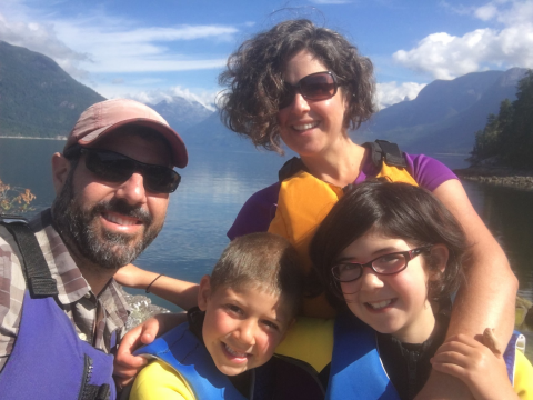 A man, a woman, and two kids all wearing life vests with a body of water and a mountain landscape in the background.