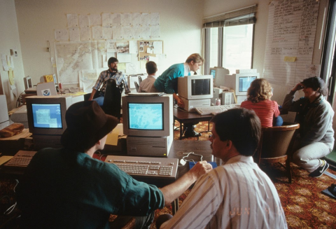 An old photo of people working on computers.