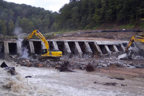 Excavation equipment moving rubble from a dam.