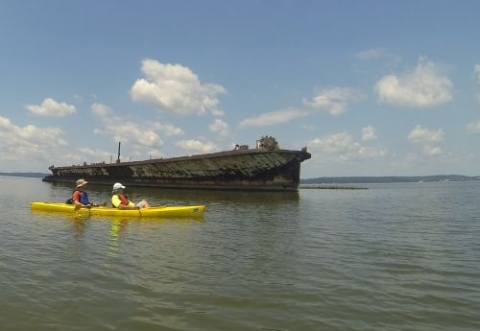 Two people in a kayak paddling in front of a wooden vessel.