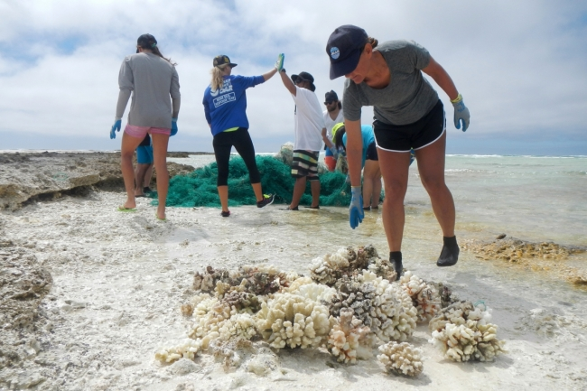 A group of people on a peach with a pile of coral in the foreground and a pile of derelict fishing gear in the background.