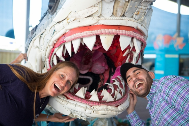 Two people stick their heads into a shark sculpture.