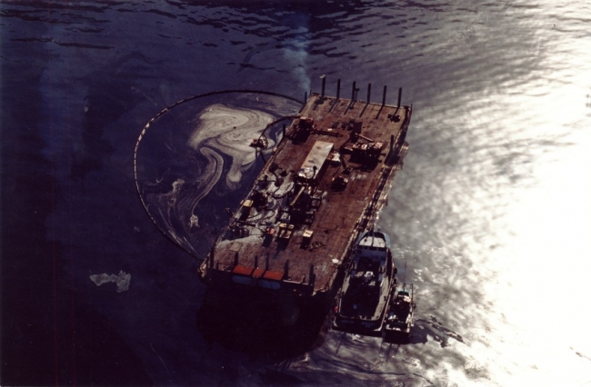 An aerial view of an oil slick next to a vessel.