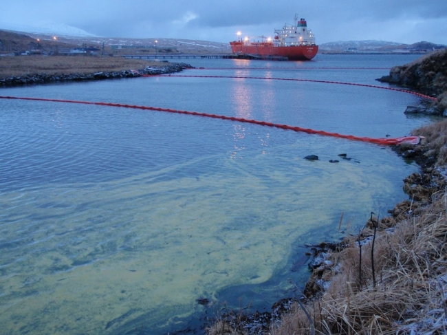 A yellow substance in the water with several lines of pollution boom and a large vessel visible in the background.