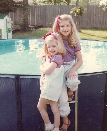 Two girls in front of a pool.