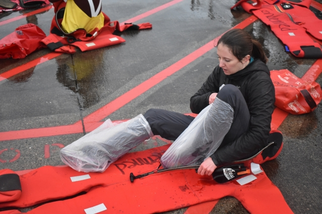 A woman with plastic bags on her feet reaches her feet into a survival suit.