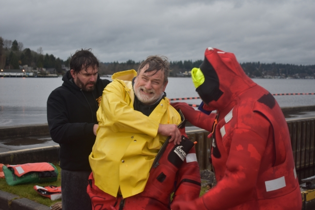 Two people help a man in a yellow rain slicker put on a survival suit