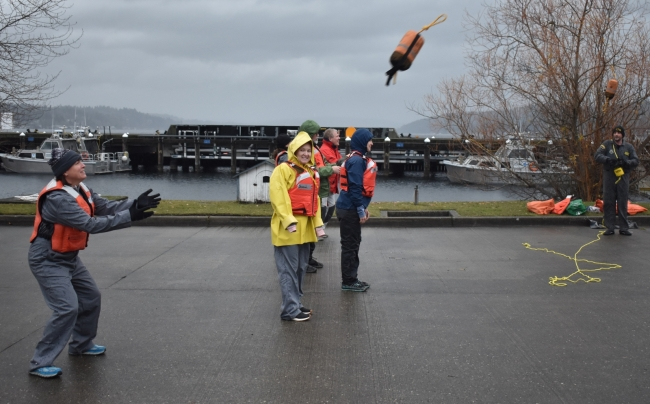 A woman in a life preserver reaches out her arms to catch a flying object.