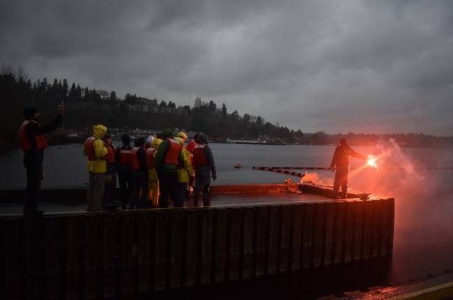 A man holding a flare at the end of a dock with a group of people on it.