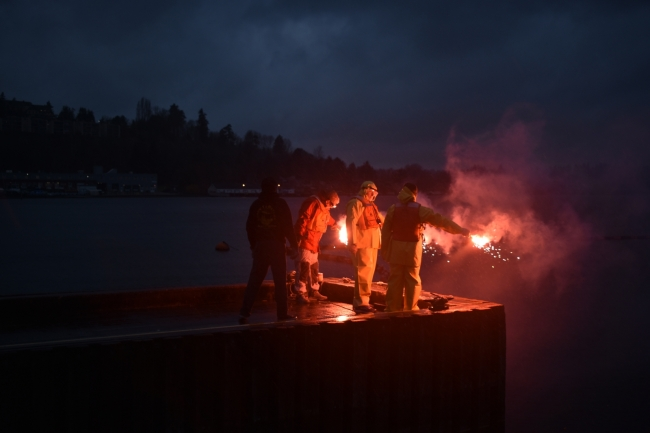Three people holding flares at the end of a dock.