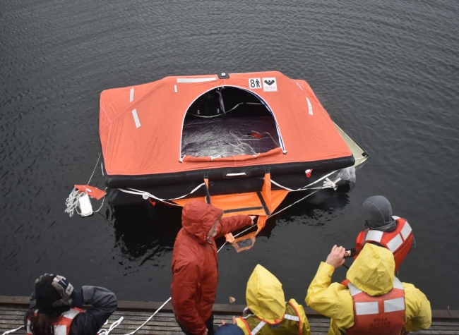 A group of people in response gear standing on a dock looking at a life raft.