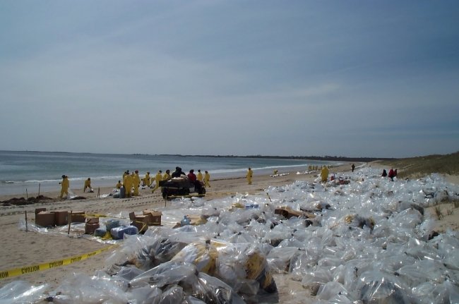 A beach covered in plastic bags filled with oil-soiled materials and cleanup workers in yellow protection gear.