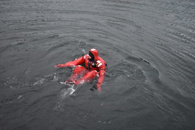 A person in a survival suit in the water.