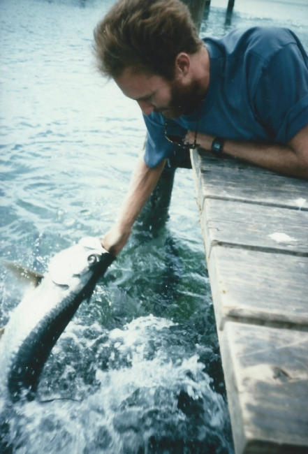 A person on a dock feeding a large fish.