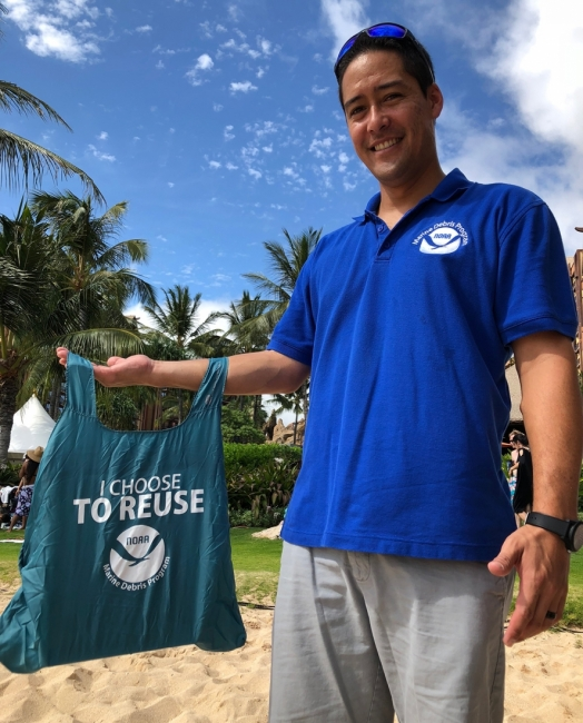 "A man holding a reusable bag that reads ""I Choose to Reuse."""