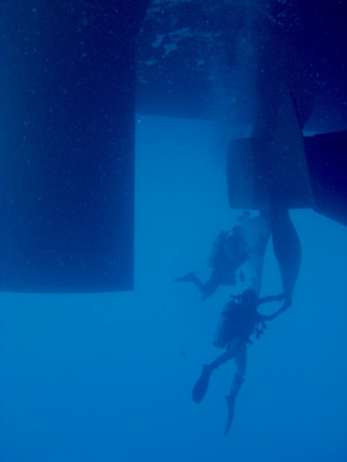 An underwater image of two underwater divers near a ship's propellers.