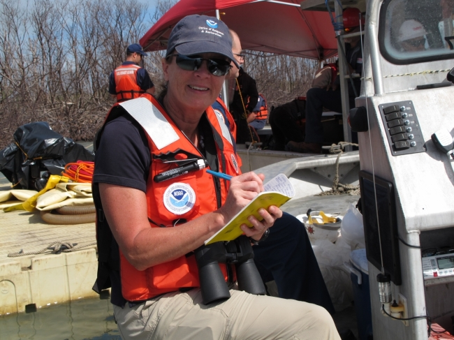 A woman in a life jacket writing in a notebook.