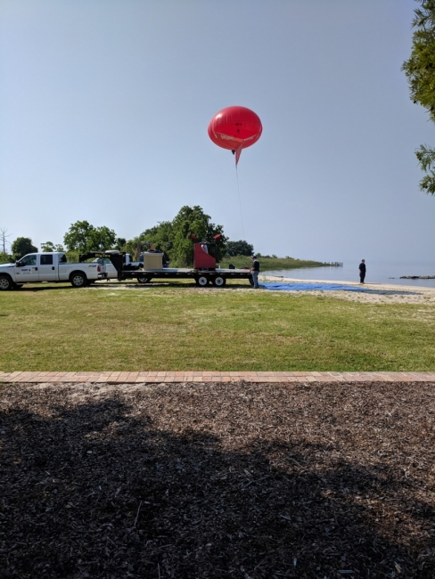 A large ballon-like object floating about a park area.