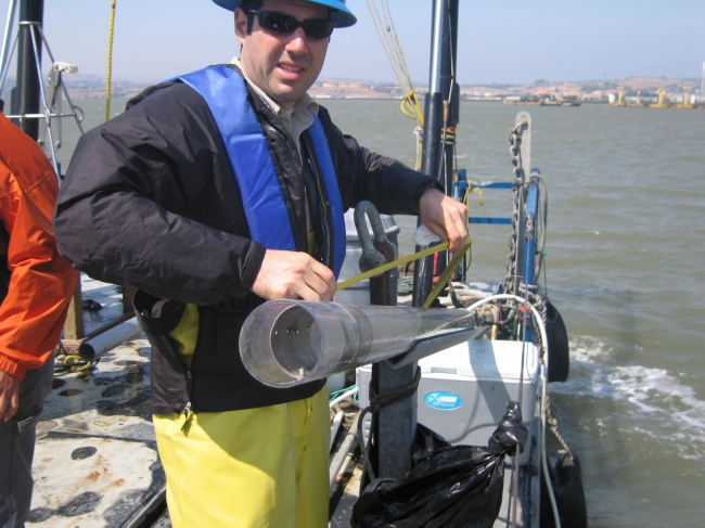A man on a boat holding a piece of tubing.