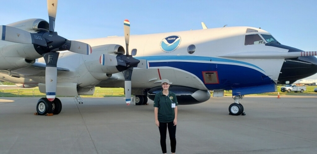 A girl standing in front of a plane with a NOAA logo on it.