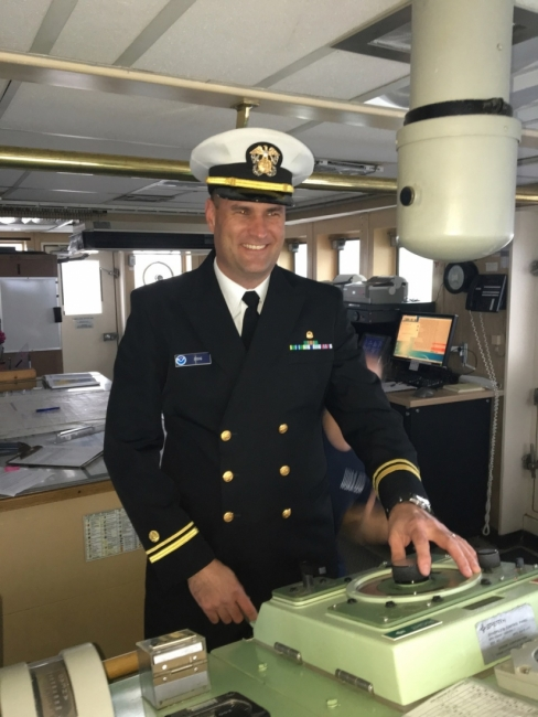 A man in a ship captain's uniform in the control room of a ship.