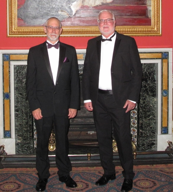 Two men in tuxedos posing for a photo.
