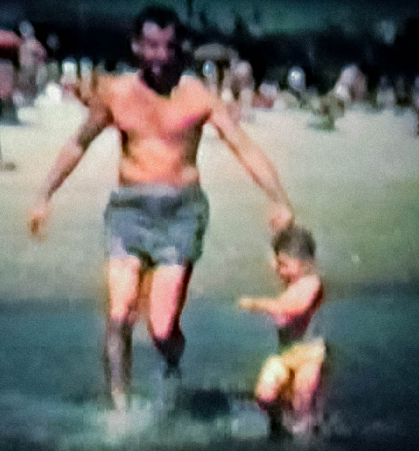 A man and a child on a beach.