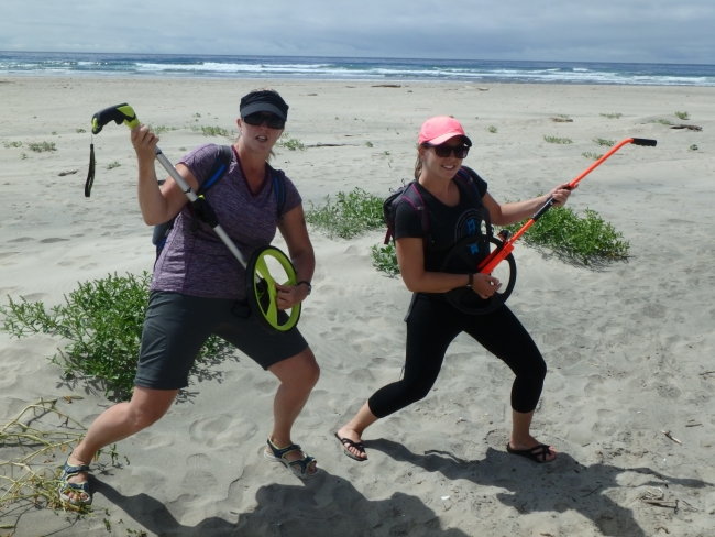 Two women strumming surveyor wheels like guitars on a beach.