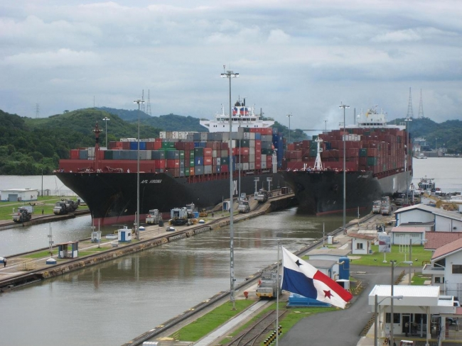 Two container ships passing through canal locks.