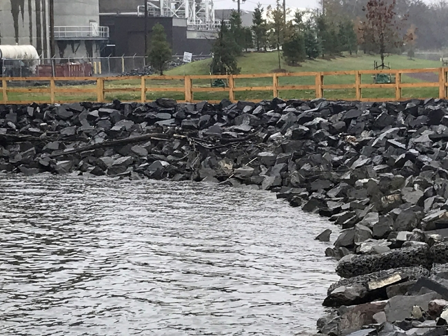 A rocky shoreline with a park and an industrial area sitting behind a wooden fence.