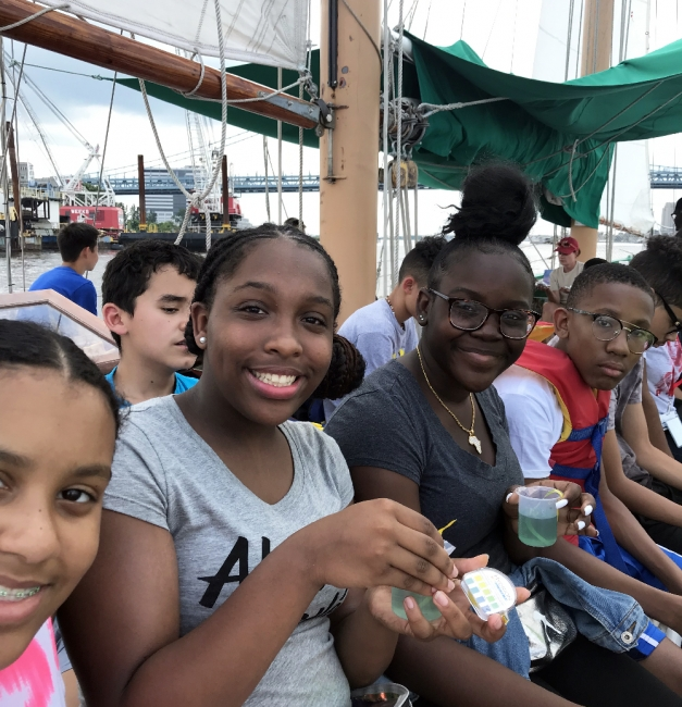 Group of teenagers aboard sailboat.