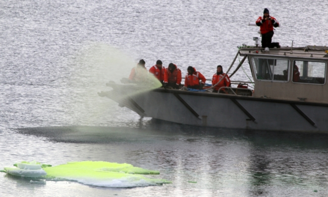 A group of people in orange gear spraying a green liquid from a boat and into the water.