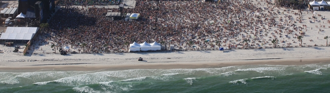 An aerial photo of a beach packed with people.