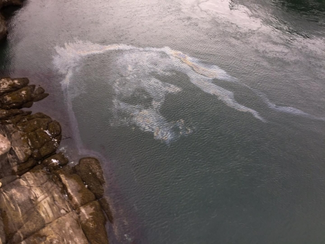 An aerial image of an oil sheen in a body of water.