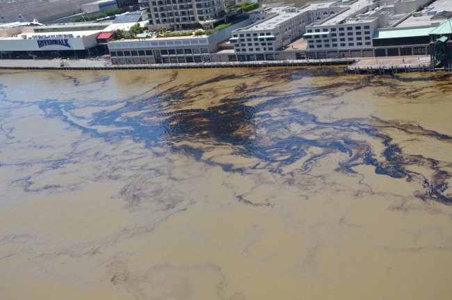 An aerial view of oil in water along an urban shoreline.