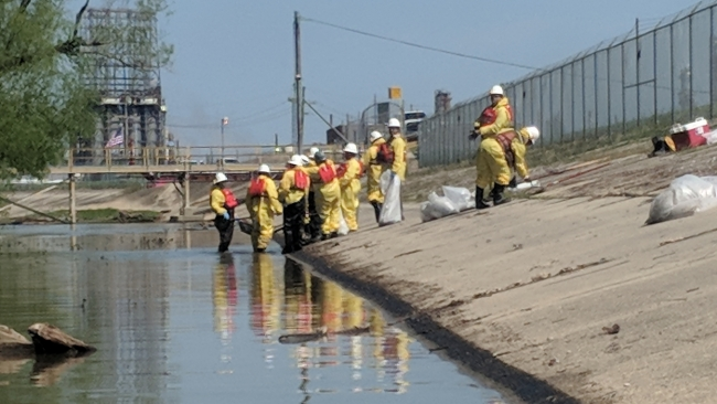 A cleanup crew working on an oiled concrete shoreline.
